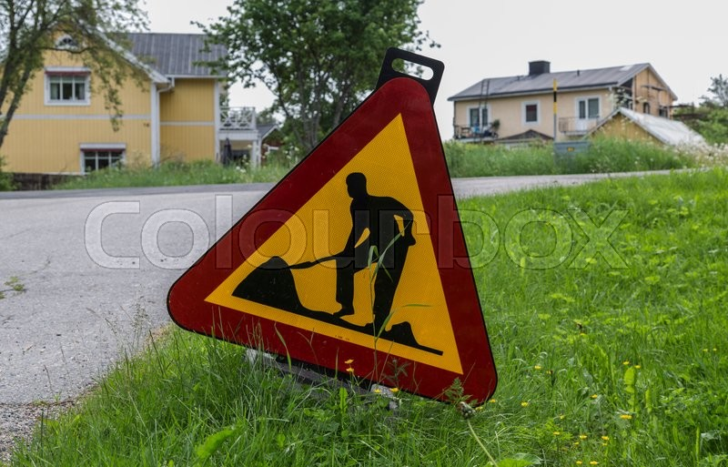 Stock image of 'A road work sign in front of some houses'