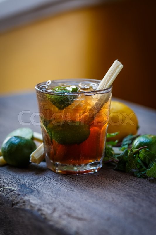 Stock image of 'Cocktail glass on wooden table with lime and lemon'