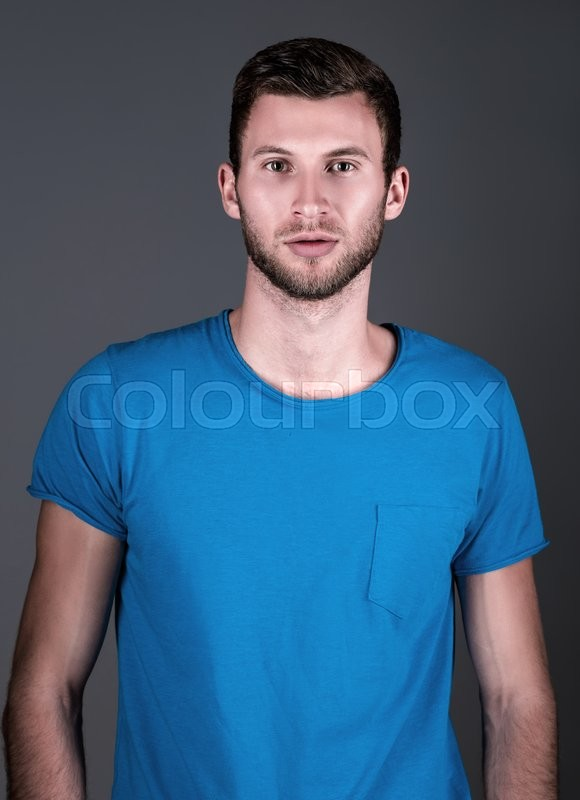 Stock image of 'Studio fashion shot: portrait of a handsome young man in blue shirt '
