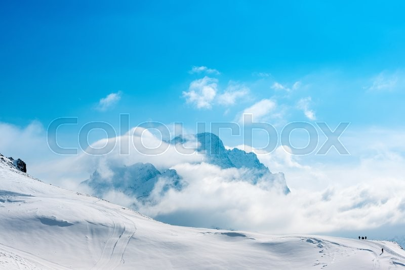 Stock image of 'beautiful winter landscape of Dombaj with blue sky, clouds and descent from the mountain, Russia '