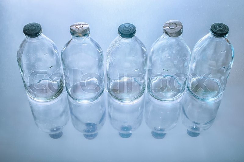 Stock image of 'top view of dirty empty vintage glass medicine bottles with stopper on blue background '