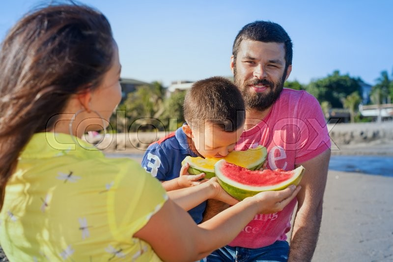 Stock image of 'Happy family funny picnic on sea beach - mother feed baby boy, adult man. Father, son eat fruits with fun. Active parents lifestyle and people outdoor activity on summer vacation with child on Bali.'