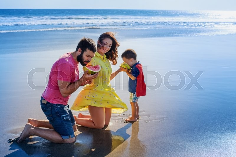Stock image of 'Happy family funny picnic on beach with sea surf - mother feed baby boy, adult man. Father, son eat fruits with fun. Active parents and people outdoor activity on summer vacation with child on Bali.'