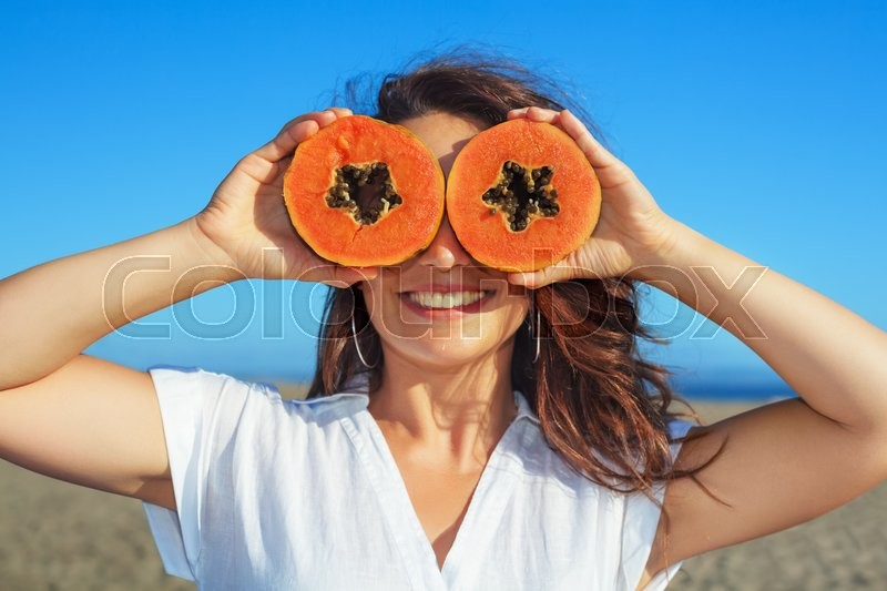 Stock image of 'Funny photo of positive adult woman with smiling face holding in hands ripe fruit - orange papaya slices. Healthful food, low calories breakfast on sea beach Healthy lifestyle on summer family holiday'