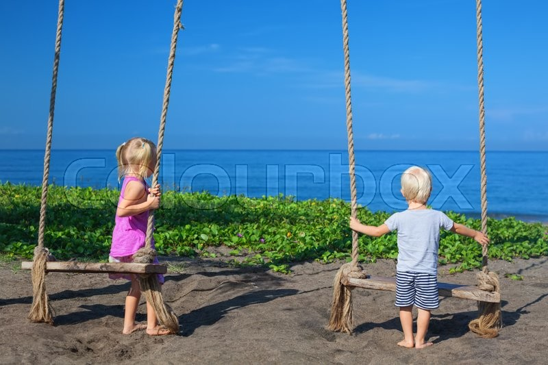 Stock image of 'Caucasian little sibling - girl and boy have fun together on rope swing, look at black sand beach, sea surf on tropical island. Travel lifestyle, people activity on summer family vacation with child.'
