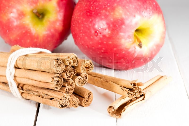 Stock image of 'cinnamon sticks with apple on kitchen table ready for cooking a recipe'