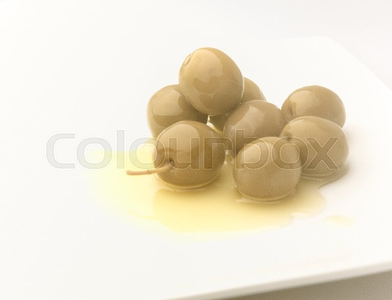 Stock image of 'A pile of olives on a olive oil on a white canvas with texture. It is a double exposure photo with a soft and beautiful effect on the main subject'