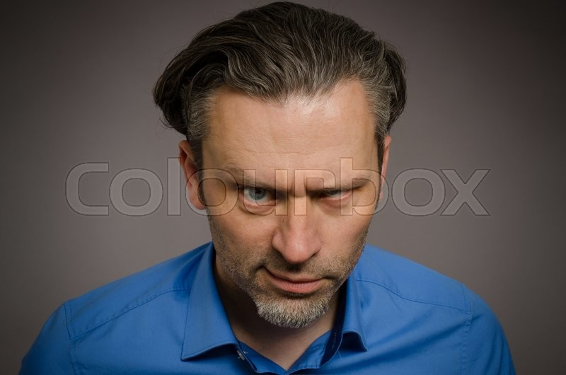 Stock image of 'Business man looking crazy on a studio background'