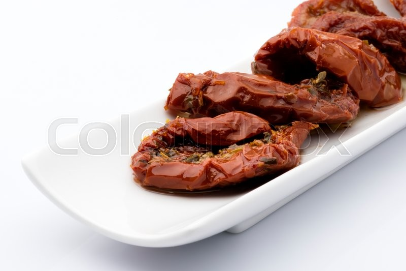 Stock image of 'dried tomatoes snack in a beautiful dish on a white background'