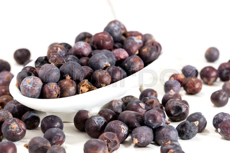 Stock image of 'juniper berries on a white wooden table'