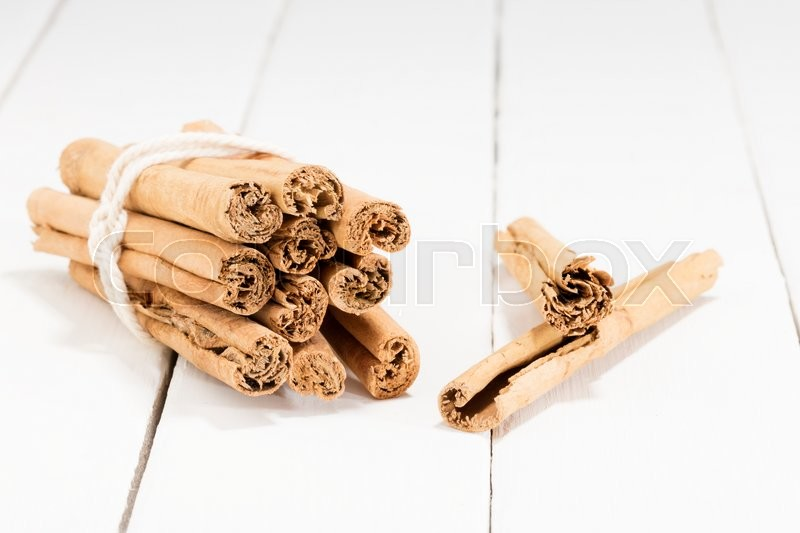 Stock image of 'cinnamon sticks on a white kitchen table'