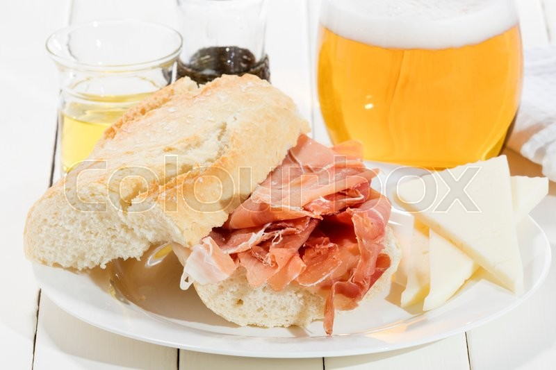 Stock image of 'cured ham sandwich with olive oil cheese and cold beer'