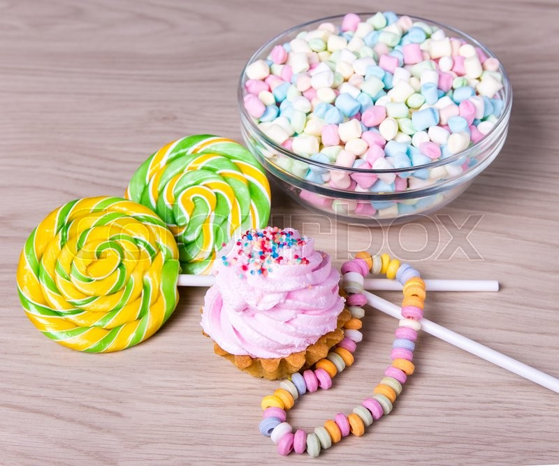 Stock image of 'mini marshmallows in glass bowl, lollipop candies and cup cake on wooden table'