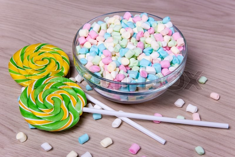 Stock image of 'colorful mini marshmallows and lollipops on wooden table background'