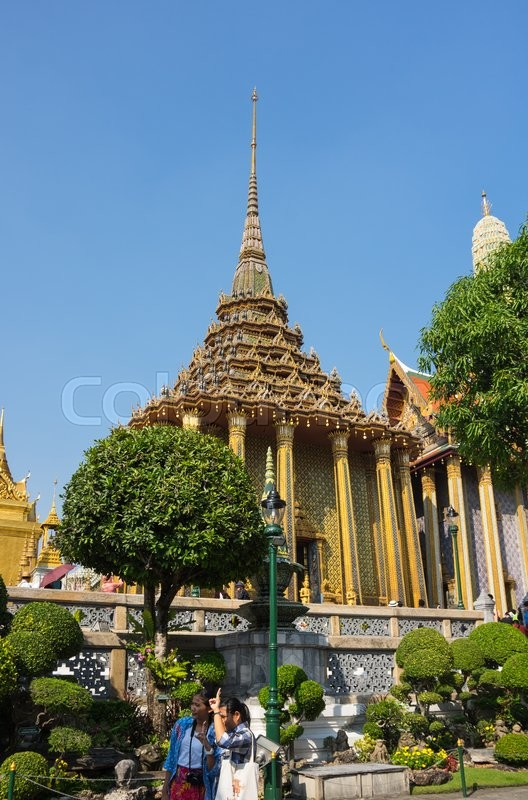Editorial image of 'BANGKOK, THAILAND - JANUARY 24, 2015: Unidentified tourists at Wat Phra Kaew in Bangkok, Thailand. Wat Phra Kaew is one of the most popular tourists destination in Thailand.'