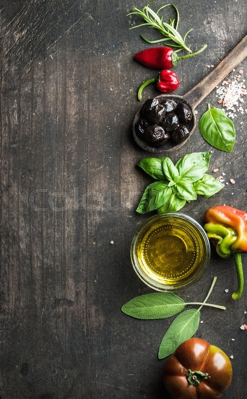 Stock image of 'Food background with vegetables, herbs and condiment. Greek black olives, fresh basil, sage, rosemary, tomato, peppers, oil on dark rustic wooden background.  Top view, copy space. Vertical'