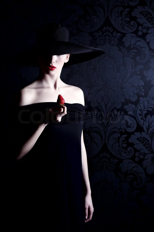 Stock image of 'Woman in black dress and hat with red lipstick holding a strawberry '