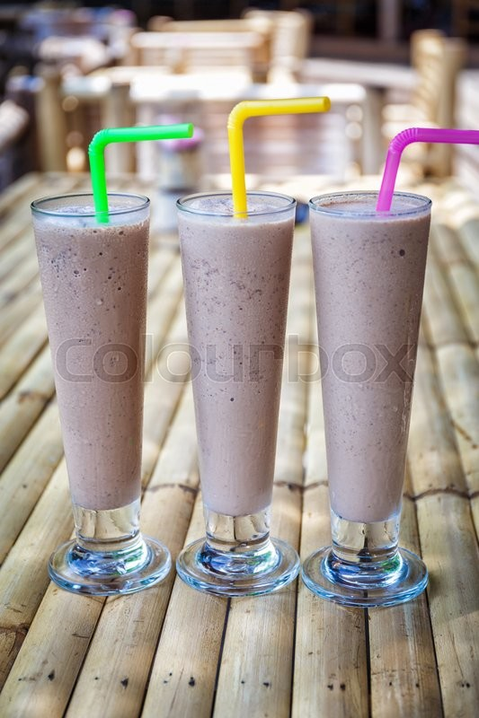Stock image of 'Chocolate milkshakes on bamboo table in cafe '