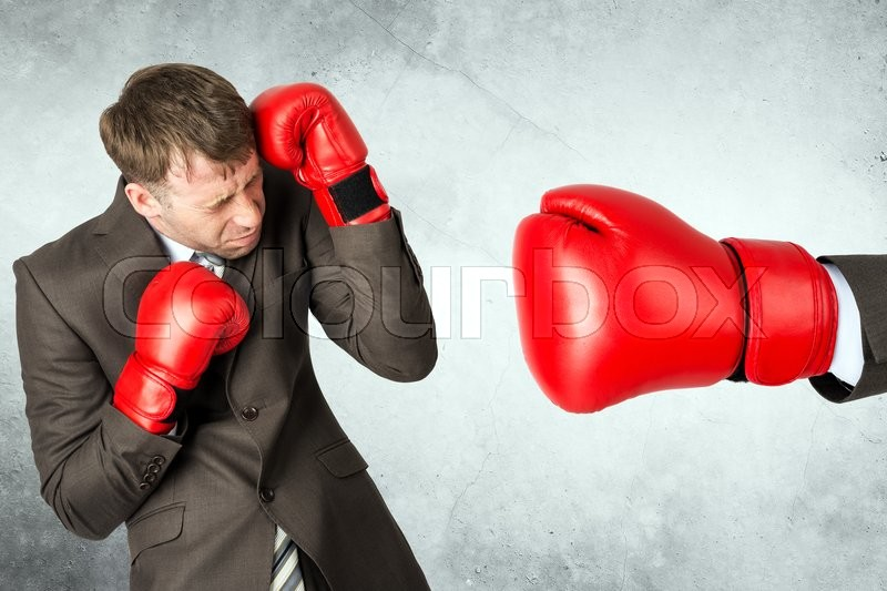 Stock image of 'Businessman in boxing gloves against big red boxing glove'