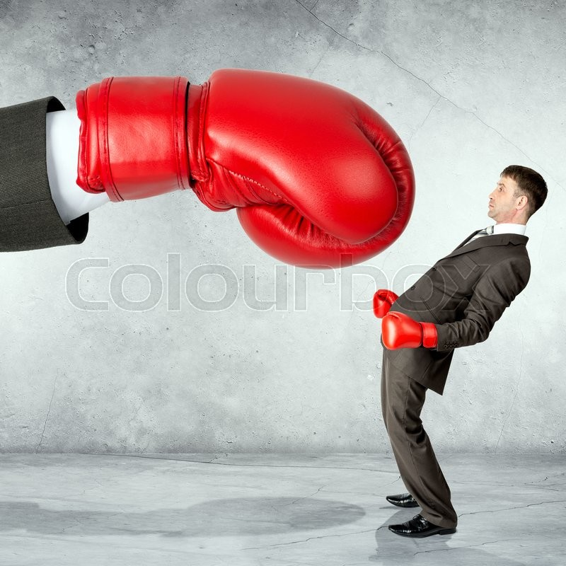 Stock image of 'Businessman in boxing gloves against big boxing glove'