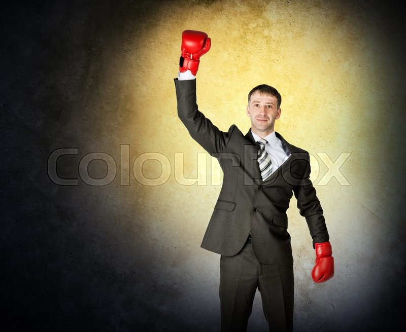 Stock image of 'Portrait of a successful businessman on grey wall background with light'