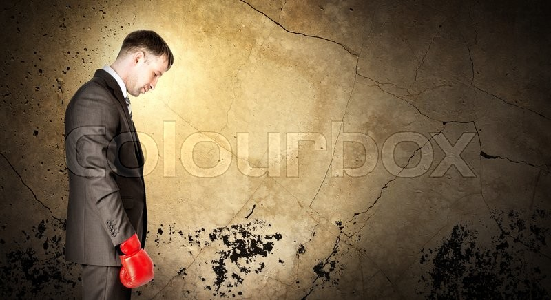 Stock image of 'Businessman wearing boxing gloves and looking sad on grey wall background with light'