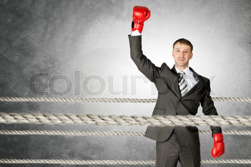 Stock image of 'Portrait of a successful businessman on boxing ring'
