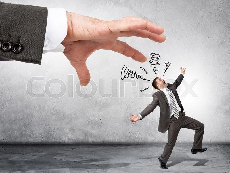 Stock image of 'Business boss hand catching scared employee on grey wall background'