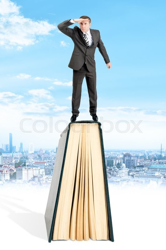 Stock image of 'Businessman standing on book and looking away on city background'