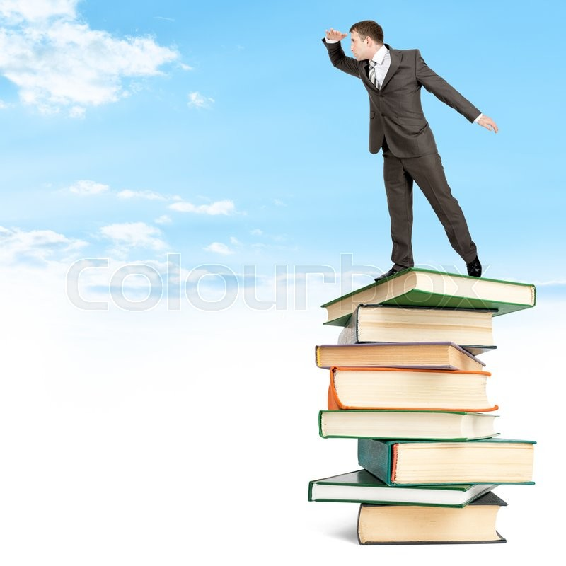 Stock image of 'Businessman staying on pile of books on top among clouds and looking into distance'