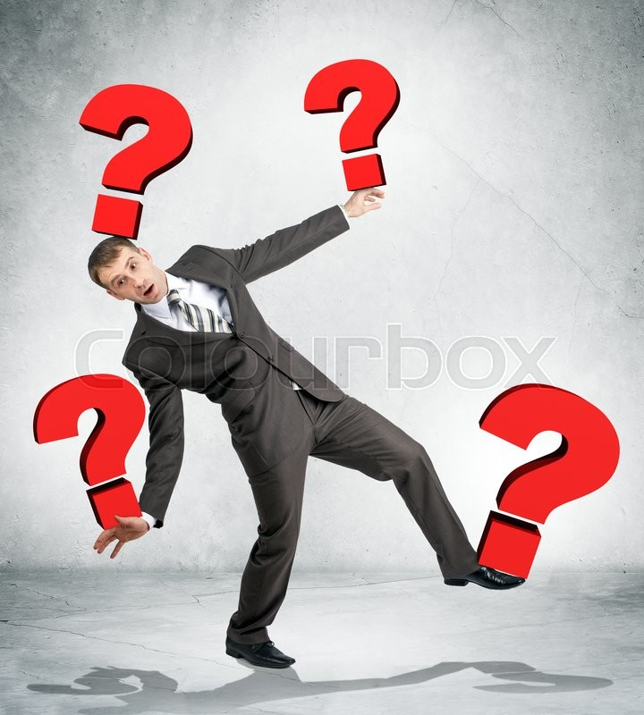 Stock image of 'Portrait of businessman holding red question marks on grey wall background'