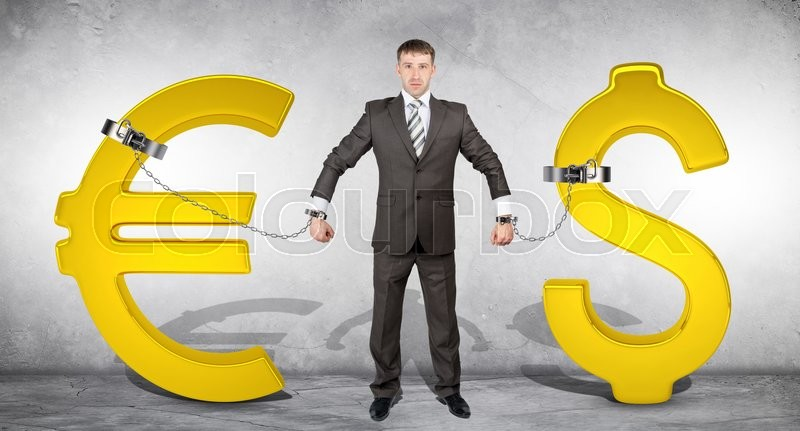 Stock image of 'Man chained with golden dollar and euro signs on grey bckground'