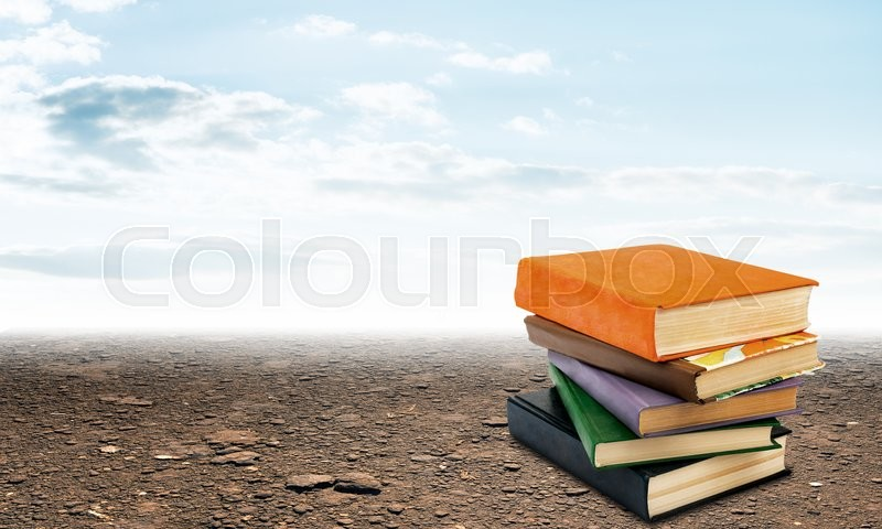 Stock image of 'Stack of books on ground with sky view background'
