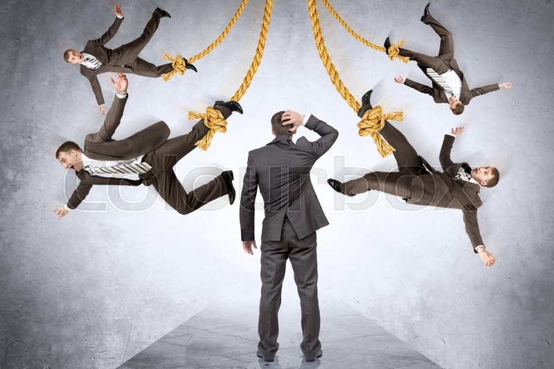 Stock image of 'Confused businessman looking on hanging people on rope'