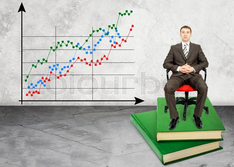 Stock image of 'Businessman sitting on books with chart on wall'