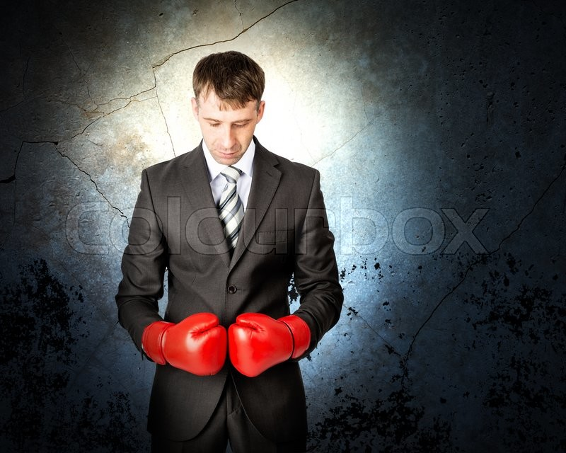 Stock image of 'Businessman with boxing gloves on grey wall background with light'