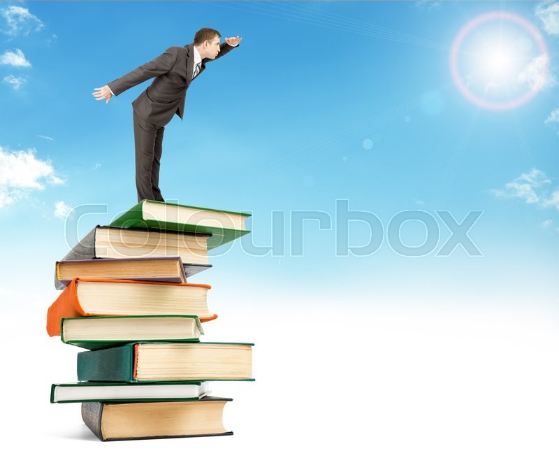 Stock image of 'Businessman staying on pile of books on top in sky and looking into distance'
