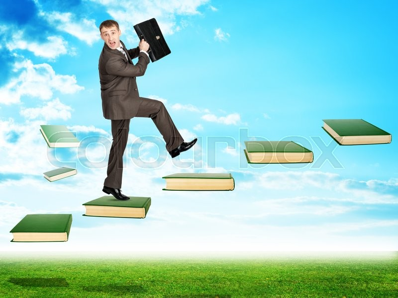 Stock image of 'Businessman walking on books in sky with green grass'