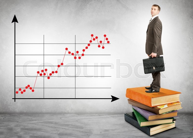Stock image of 'Businessman standing on books with chart on wall'