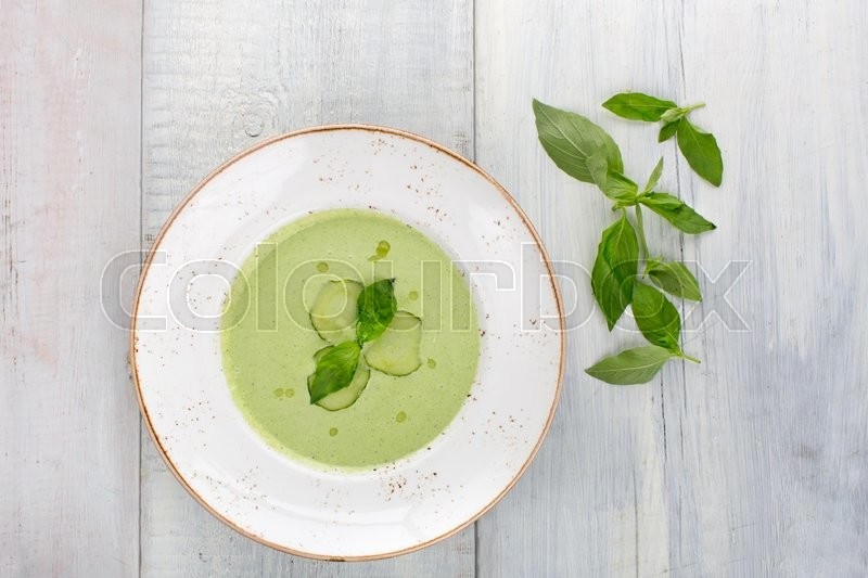 Stock image of 'Cold cucumber soup with basil, green on a white wooden background, top view'