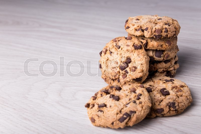 Stock image of 'close up of chocolate chip cookies stacked on wooden table background'