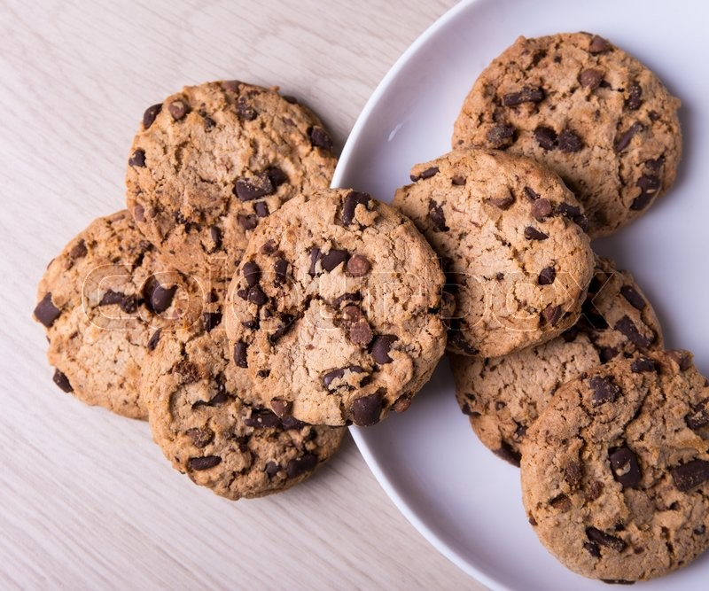 Stock image of 'top view of chocolate chip cookies on wooden table background'