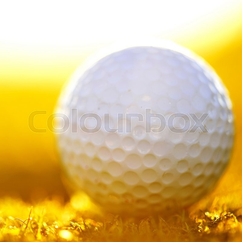 Stock image of 'Green field and white golf ball sanset'
