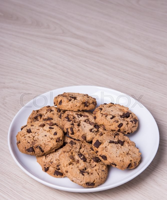 Stock image of 'close up of chocolate chip cookies on white plate and copy space on wooden table background'