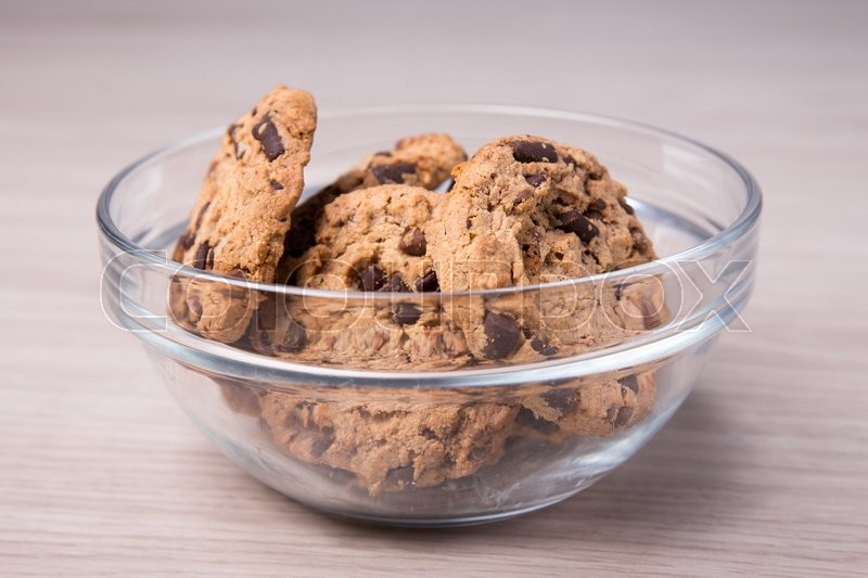 Stock image of 'chocolate cookies in glass bowl on wooden table background'