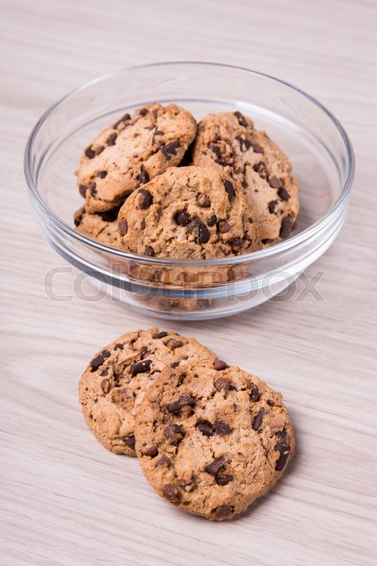 Stock image of 'chocolate chip cookies in glass bowl on wooden table background'