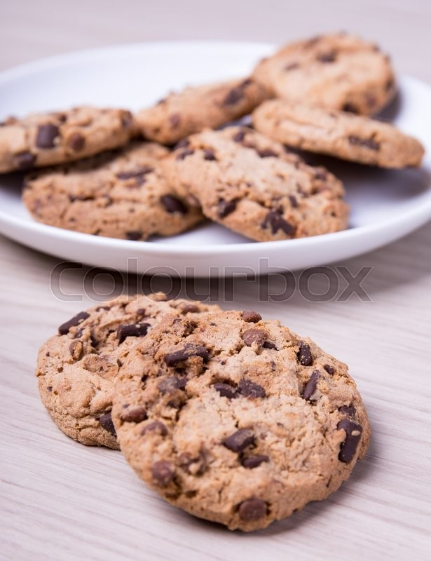 Stock image of 'close up of chocolate chip cookies on wooden table background'