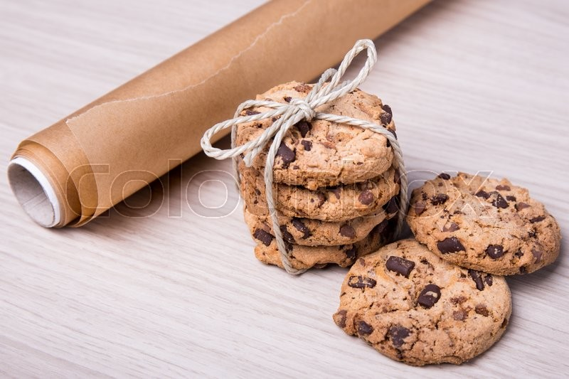 Stock image of 'close up of chocolate chip cookies and parchment paper on wooden table background'