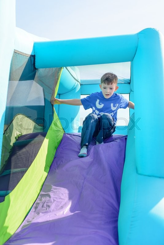 Stock image of 'Cute little boy sliding down blue and purple inflatable outdoor carnival amusement ride'