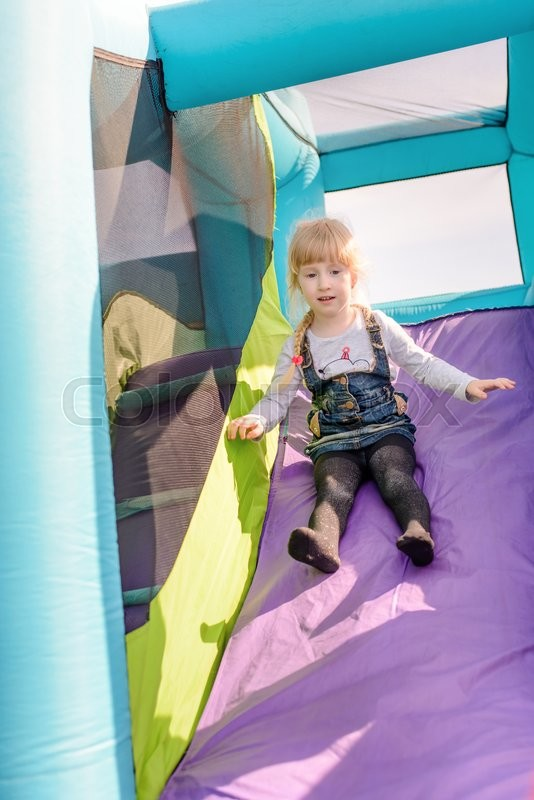 Stock image of 'Cute little girl with static electrically charged hair sliding down onto landing for blue, green and purple inflatable outdoor carnival amusement ride'